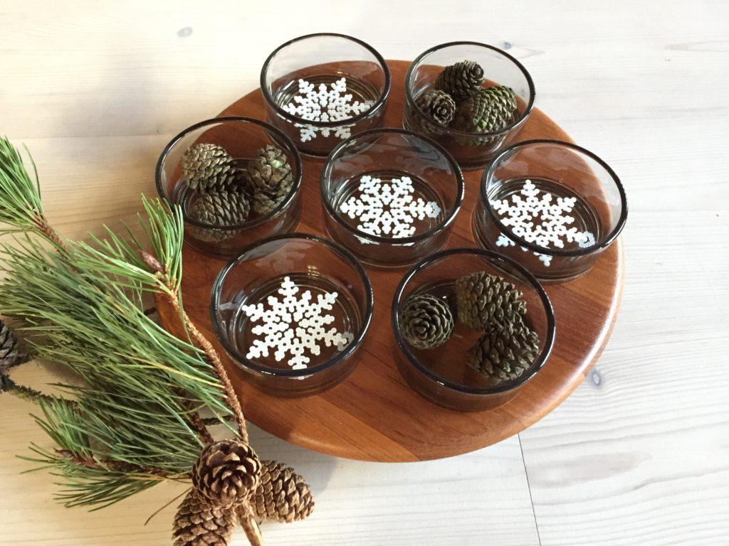 Forskellige snefnug af miniperler samt fyrkogler i smukt cabaretfad af teak