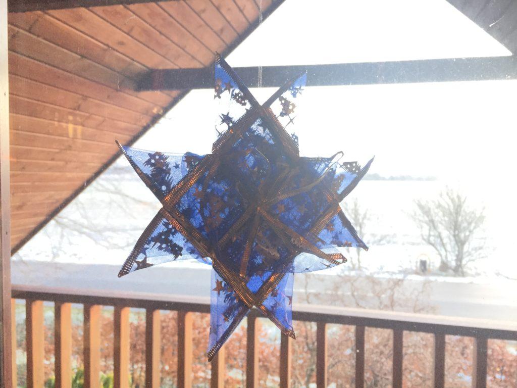 Flettet stjerne i krølbånd i vinduet med sne og sol