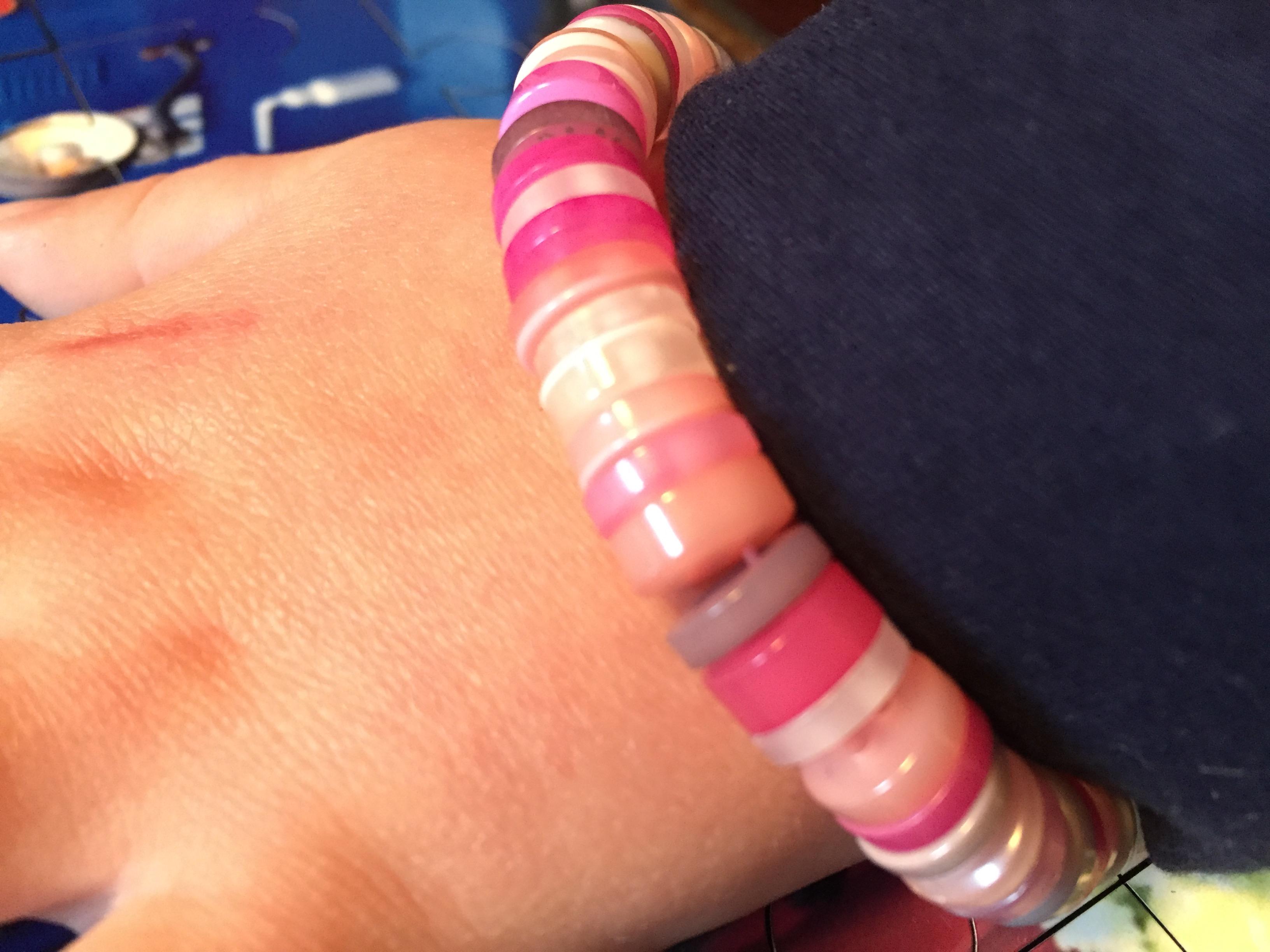 Det søde armbånd af knapper på en lille arm